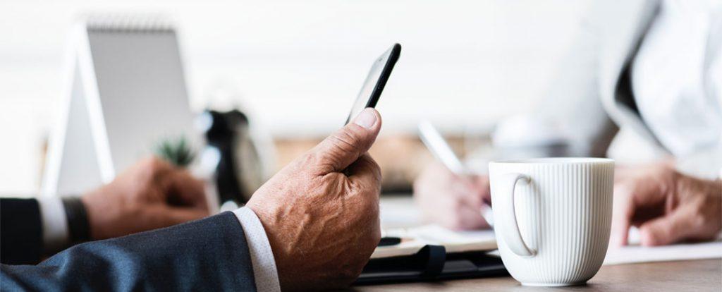 Geschäftsmann hat Handy in der Hand- symoblisch für Smartphonesucht